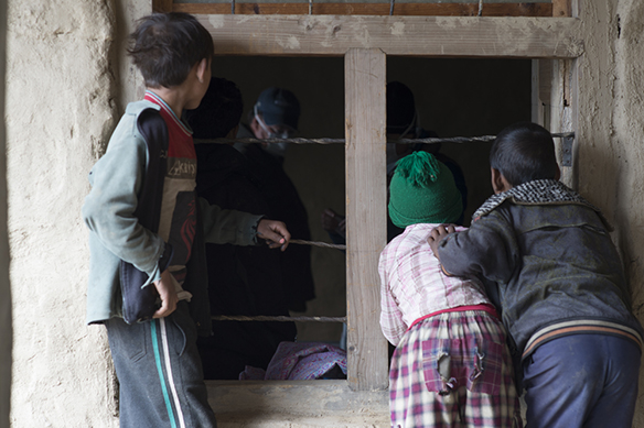 Children peeking into the windows of Humla Fund's medical clinic.