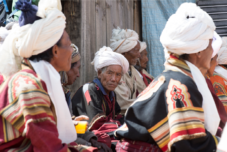 Group of Bonpo men in white turbans and native robes.
